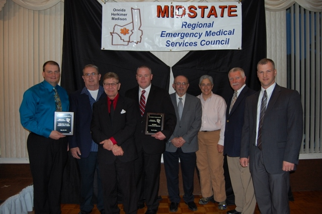 Kunkel Ambulance and Mohawk Valley Ambulance Corps (MOVAC) representatives accept the St. Elizabeth Trauma Center Life-Saving Award at the Midstate Regional EMS Council's annual awards ceremony. St. Elizabeth Trauma Center staff selected the ambulance providers for their efforts during the mass shooting tragedy in March 2013, and the two survivors of the incident helped present the award.  Pictured from left to right are MOVAC Chief Chad Smith; Dan Haslauer and John Seymour, survivors of the mass shooting; Kunkel Ambulance Director of Operations Randy Sutherland; Regional Medical Director John Detraglia; New York State EMS Bureau Director Lee Burns; Midstate Regional EMS Council Chair Butch Hoffman; and St. Elizabeth Trauma Center Trauma Program Manager Paul Campbell.